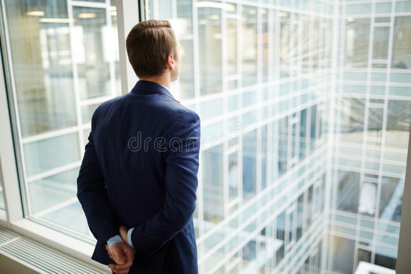 Uomo dalla finestra fotografia stock