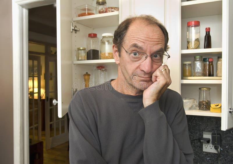 Uomo davanti agli armadi da cucina vuoti immagine stock