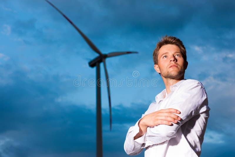 Uomo davanti al mulino a vento ed al cielo fotografie stock