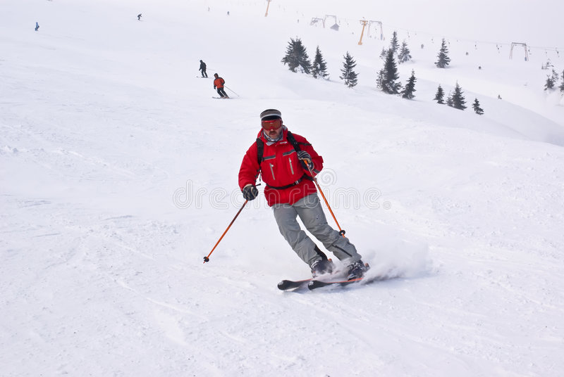 Uomo degli sciatori di Alpen che funziona giù contro gli elevatori immagine stock libera da diritti