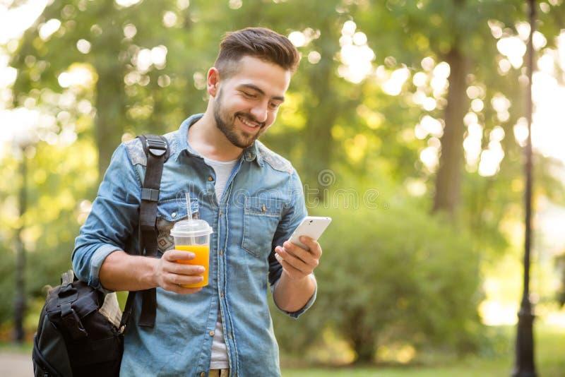 Uomo dei pantaloni a vita bassa che cammina nel parco di autunno fotografie stock