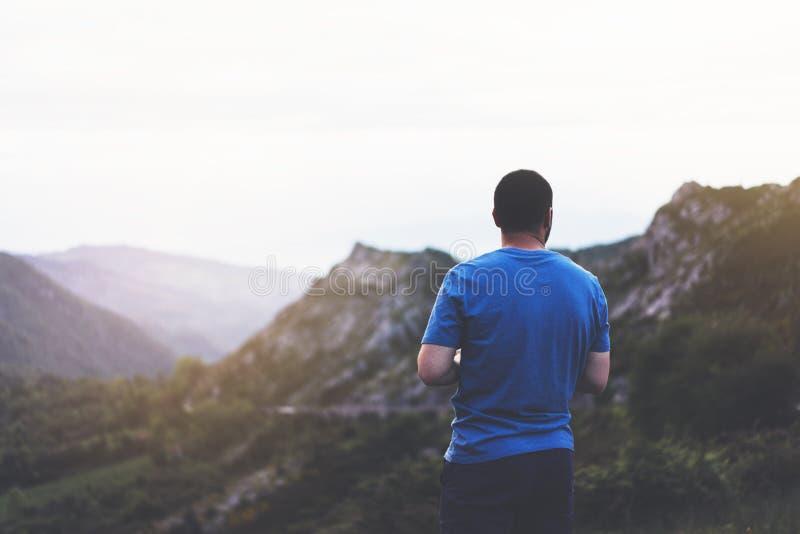Uomo dei pantaloni a vita bassa che gode del tramonto sul picco della montagna nebbiosa, viaggiatore turistico che prende le imma fotografia stock libera da diritti