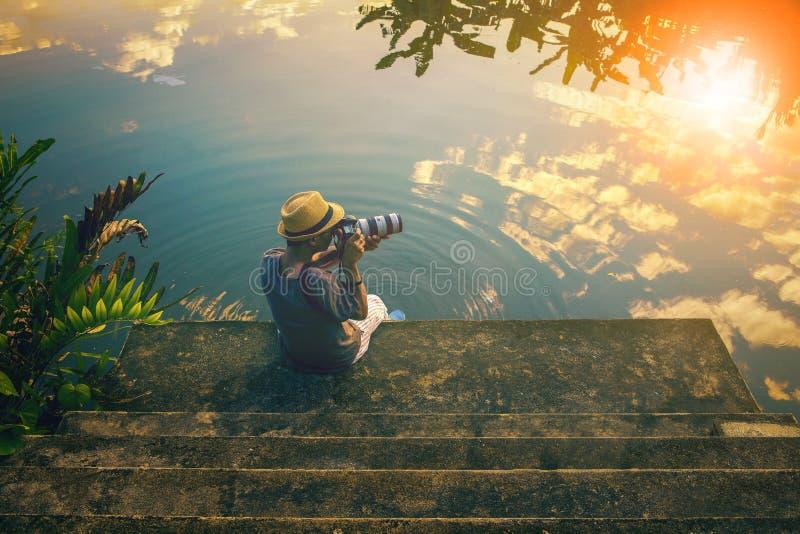 Uomo dei pantaloni a vita bassa che prende una fotografia sul pilastro contro i bei cieli immagine stock libera da diritti