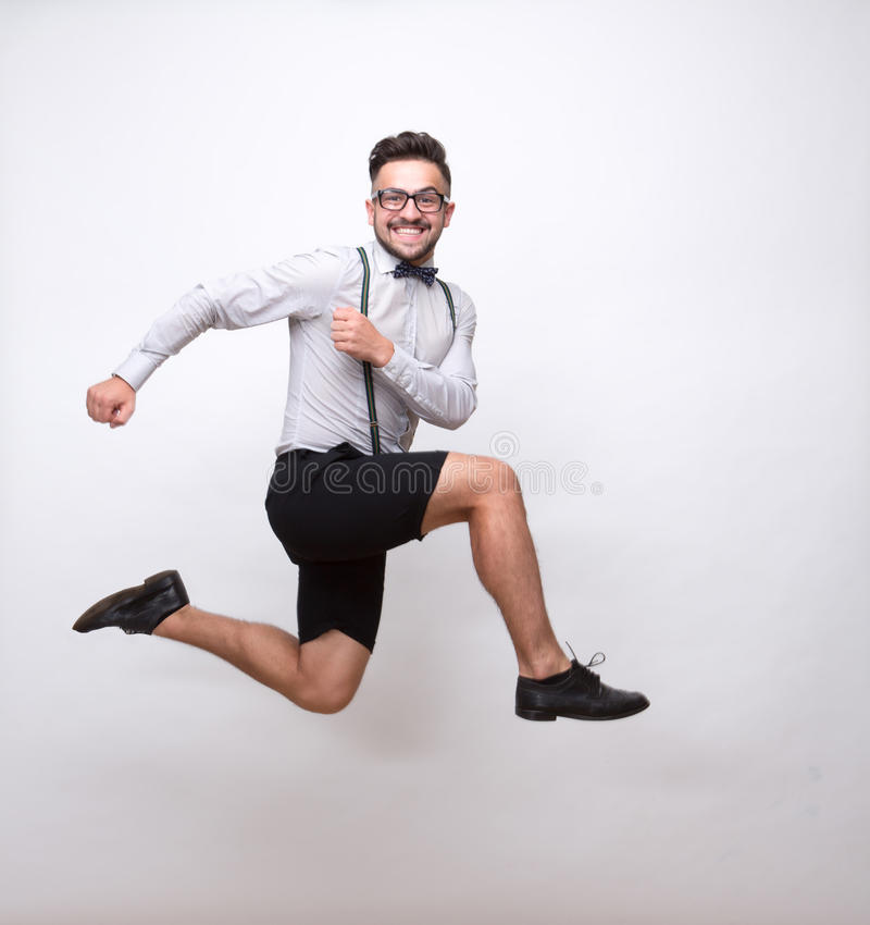 Uomo dei pantaloni a vita bassa che salta nello studio della foto fotografia stock libera da diritti