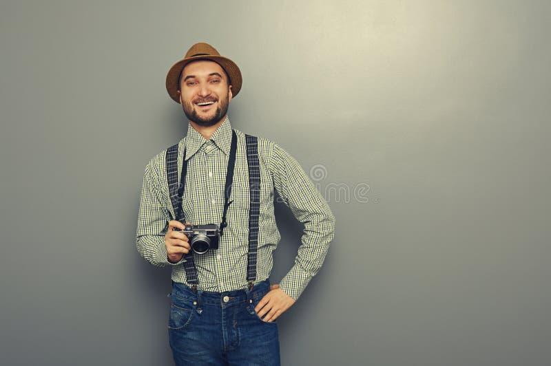 Uomo dei pantaloni a vita bassa che tiene retro macchina fotografica fotografia stock libera da diritti