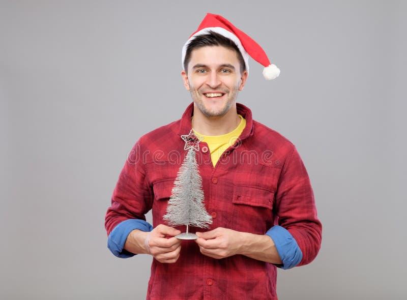 Uomo dei pantaloni a vita bassa con l'albero di Natale del cappello e di Santa Claus immagini stock libere da diritti