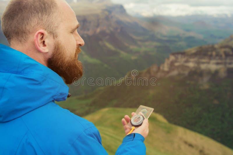 Uomo dei pantaloni a vita bassa in una giacca blu facendo uso di una bussola sui precedenti nei precedenti del paesaggio caucasic fotografia stock
