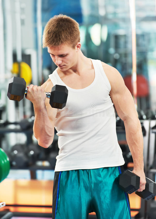 Uomo del Bodybuilder che fa le esercitazioni del muscolo del bicipite fotografie stock