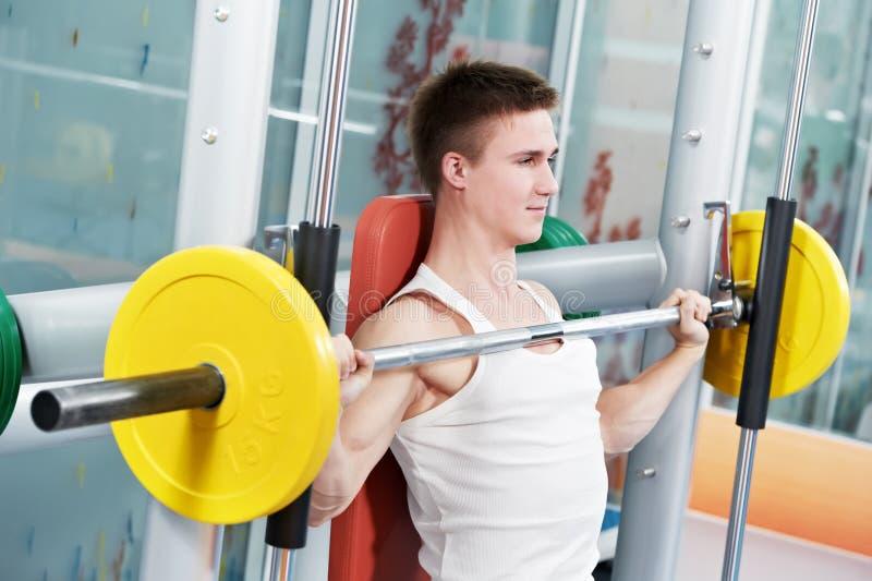 Uomo del Bodybuilder che fa le esercitazioni del muscolo del bicipite immagine stock