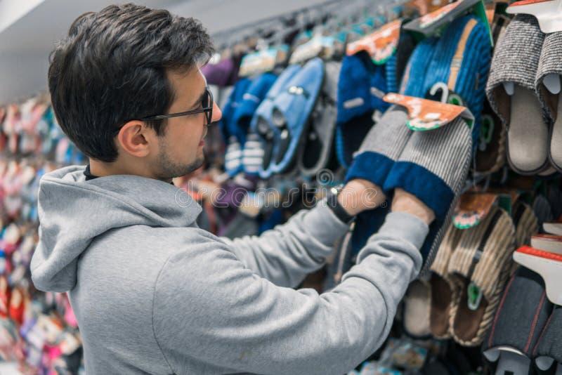 Uomo del cliente che sceglie le pantofole domestiche nel centro commerciale del supermercato fotografie stock
