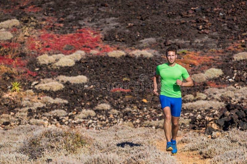 Uomo del corridore dell'atleta di sport che corre nel fondo della natura della traccia di montagna Corpo adatto motivato messo a  fotografia stock