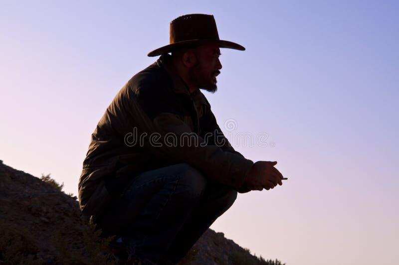 Uomo del cowboy che si siede all'alba immagine stock libera da diritti