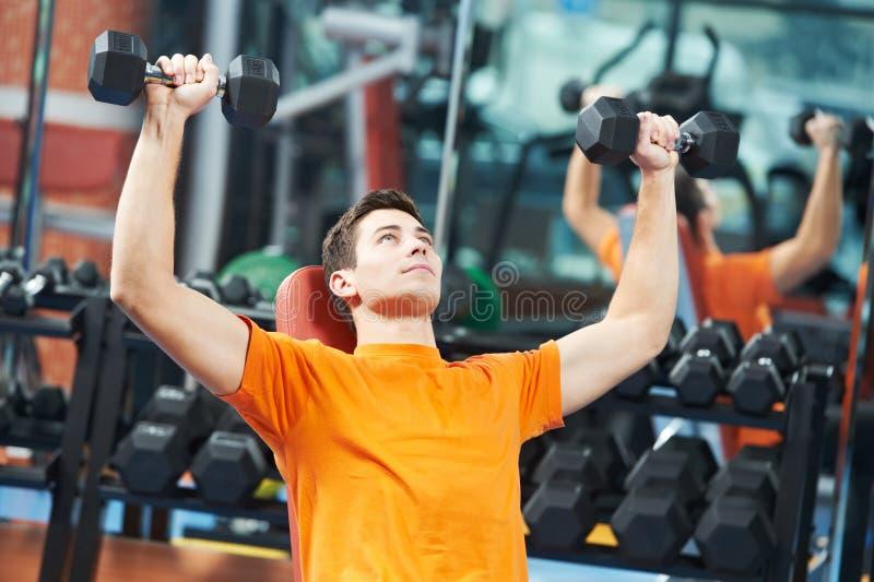 Uomo del culturista che fa gli esercizi del muscolo del bicipite immagine stock libera da diritti