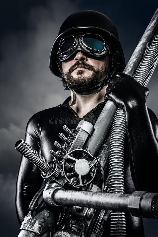 Uomo del futuro con il fucile da caccia enorme del cannone del laser fotografia stock libera da diritti