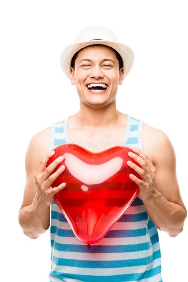 Uomo del latino che tiene il pallone rosso del cuore immagine stock libera da diritti