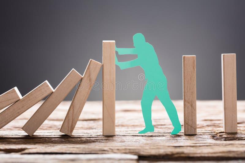 Uomo del Libro Verde che ferma i blocchetti di legno di domino fotografie stock