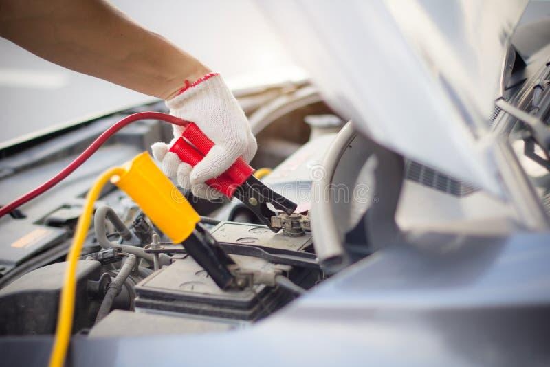 Uomo del meccanico di automobile facendo uso dei cavi di saltatore della batteria per caricare una batteria morta Fine sulla mano fotografia stock libera da diritti