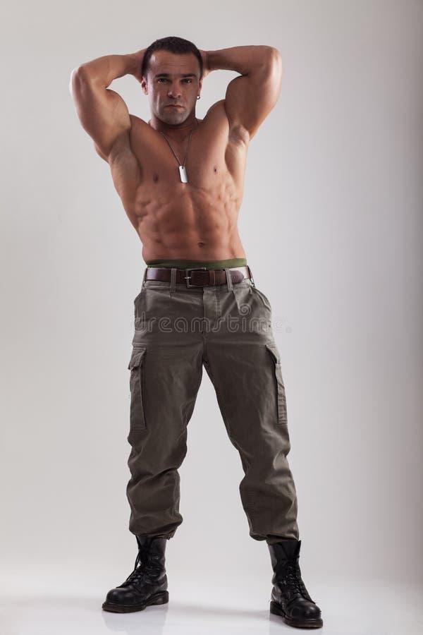 Uomo del muscolo in abbigliamento militare immagini stock