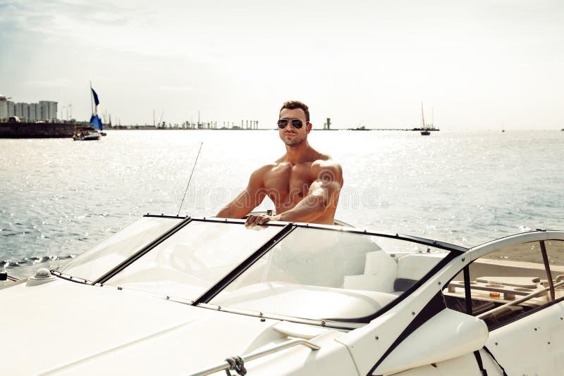 Uomo del muscolo su una barca fotografie stock