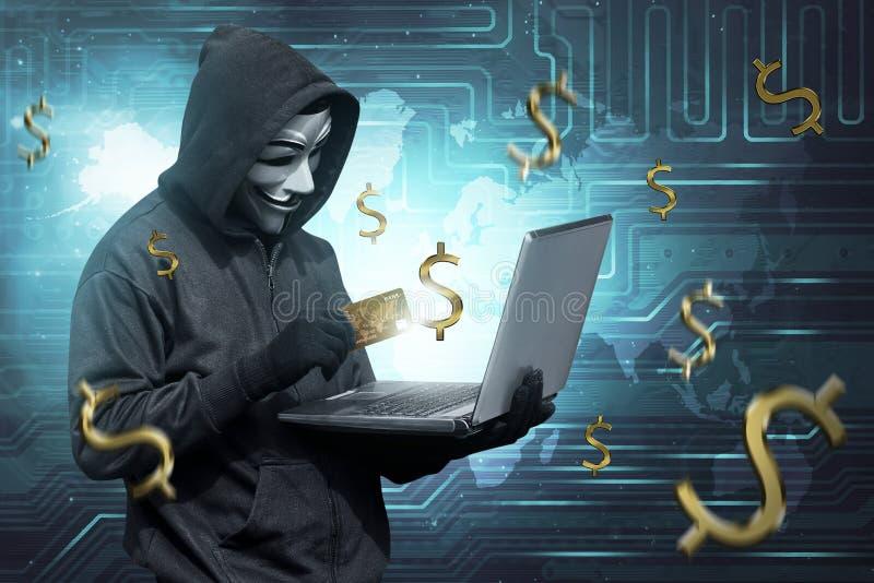 Uomo del pirata informatico con la carta di credito della tenuta della maschera con il computer portatile sulla sua mano fotografie stock