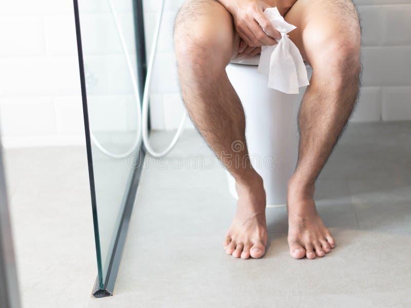 Uomo del primo piano che si siede sulla toilette con la carta velina a disposizione, fuoco selettivo fotografia stock