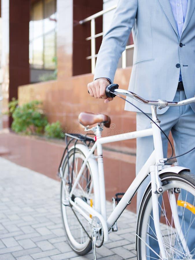 Uomo del primo piano con una bici Uomo in una bicicletta principale del vestito sui precedenti urbani Concetto dell'ambiente di r fotografia stock libera da diritti