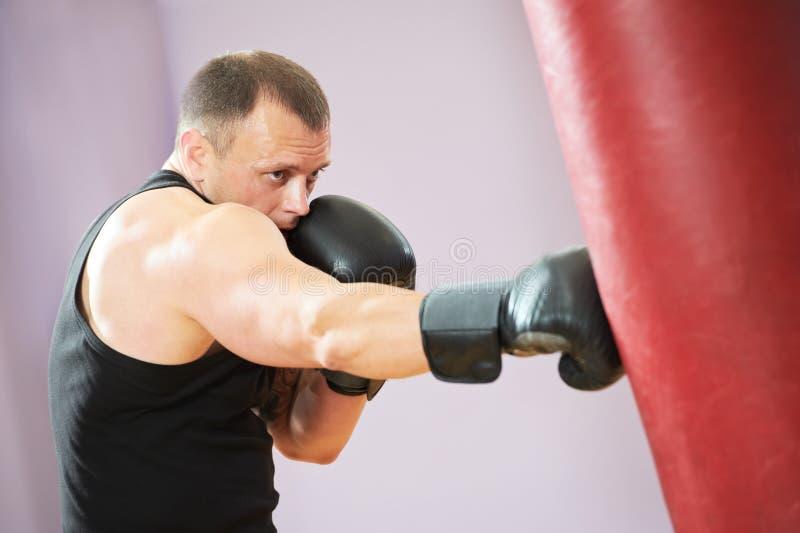 Uomo del pugile ad addestramento di inscatolamento con il sacchetto pesante immagine stock