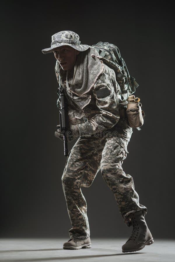 Uomo del soldato delle forze speciali con la mitragliatrice su un fondo scuro immagini stock