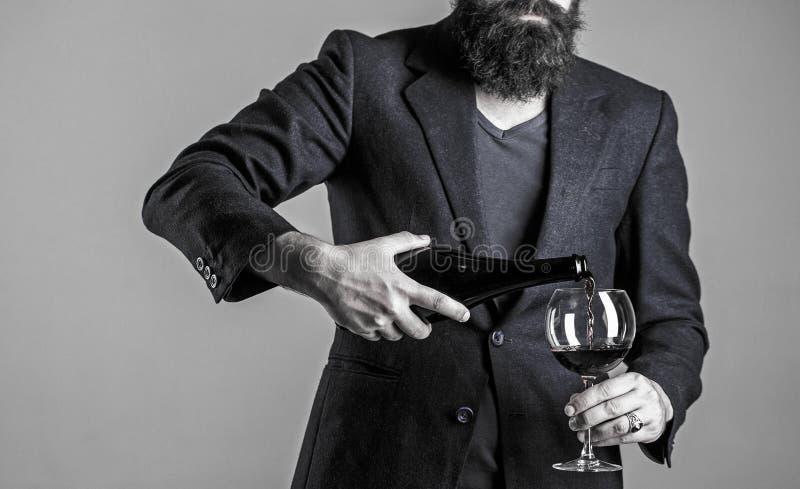 Uomo del sommelier, degustator, cantina, enologo maschio Bottiglia, vetro del vino rosso Cameriere che versa vino rosso in glas U fotografie stock