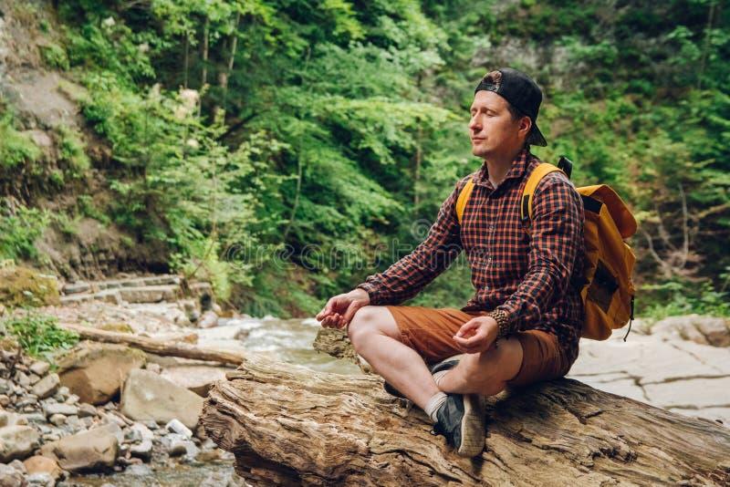 Uomo del viaggiatore in una posizione meditativa con uno zaino che si siede su un tronco di albero contro lo sfondo della foresta immagini stock libere da diritti