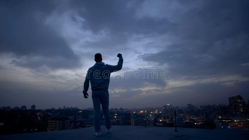 Uomo del vincitore che gode del successo sul fondo di paesaggio urbano di notte, direzione personale fotografia stock libera da diritti