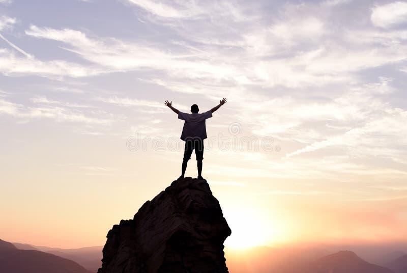 Uomo del vincitore che sta sulla cima della montagna fotografia stock