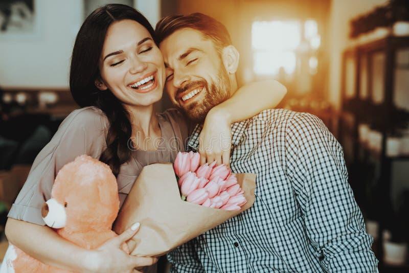 Uomo dell'abbraccio con l'orso ed i fiori Felicità con la famiglia e l'uomo bello Sorriso con la gente felice ed il buon regalo L immagine stock