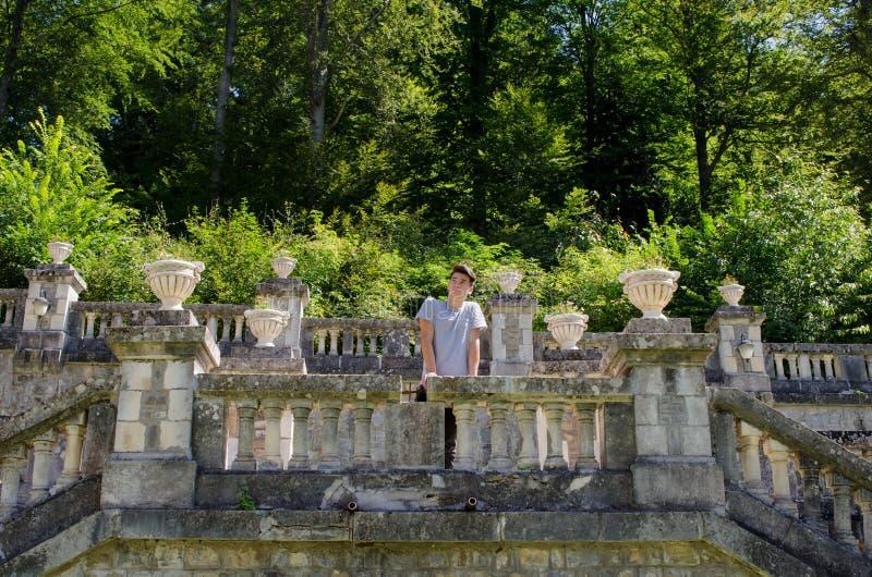 Uomo dell'adolescente che pensa sul terrazzo di pietra all'aperto al castello fotografia stock libera da diritti