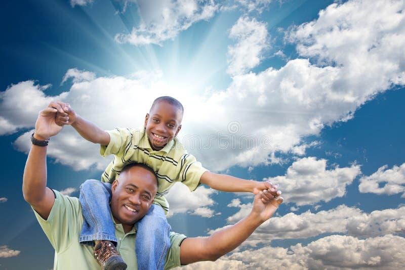 Uomo dell'afroamericano con il bambino sopra il cielo fotografia stock libera da diritti