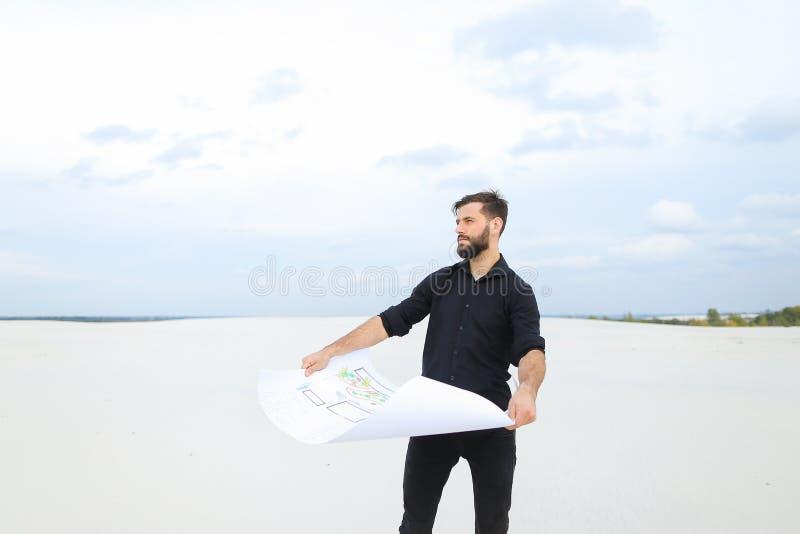 Uomo dell'archeologo che esamina piano degli scavi nella conversazione del villaggio fotografia stock