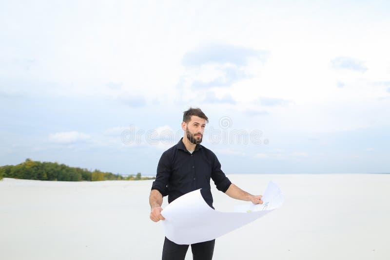 Uomo dell'archeologo che esamina piano degli scavi nella conversazione del villaggio fotografie stock libere da diritti