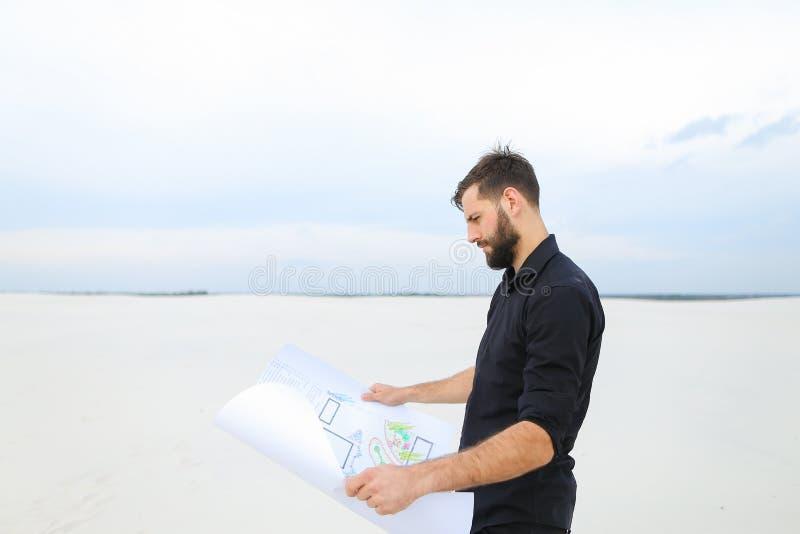 Uomo dell'archeologo che esamina piano degli scavi nella conversazione del villaggio immagine stock