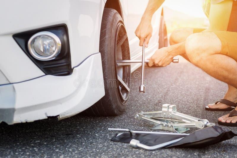Uomo dell'Asia con un'automobile bianca che ha ripartito sulla strada Gomma cambiante sull'automobile rotta immagini stock