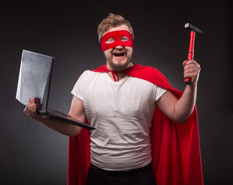 Uomo dell'eroe eccellente con il computer portatile fotografia stock