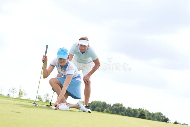 uomo dell'Mezzo adulto che esamina donna che tende palla sul campo da golf immagini stock libere da diritti