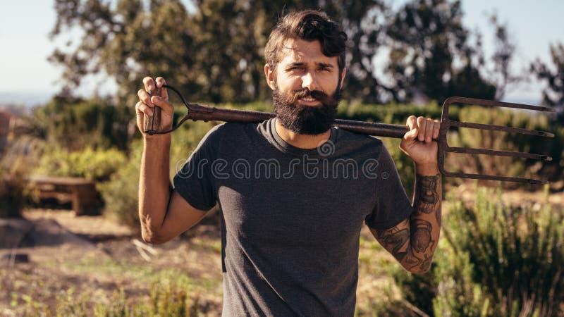 Uomo della barba con la forca sull'azienda agricola immagini stock
