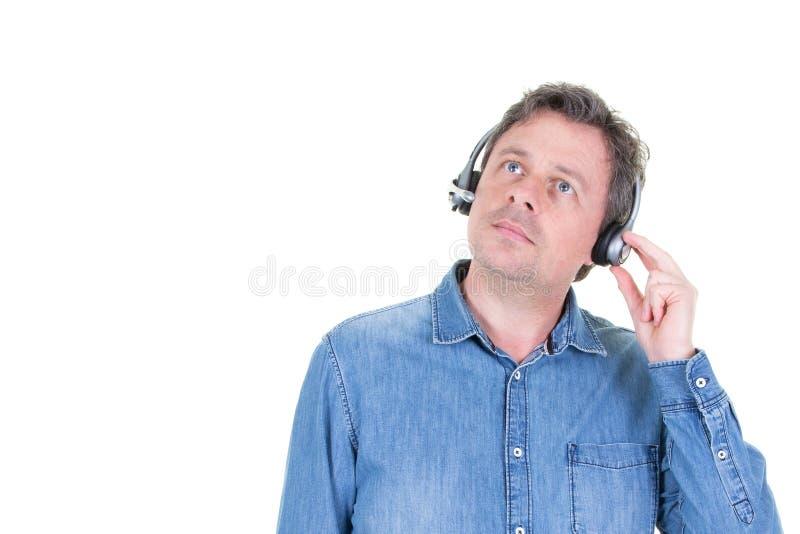 Uomo della call center che indossa una cuffia avricolare che cerca da parte lo spazio della copia nel fondo bianco immagini stock