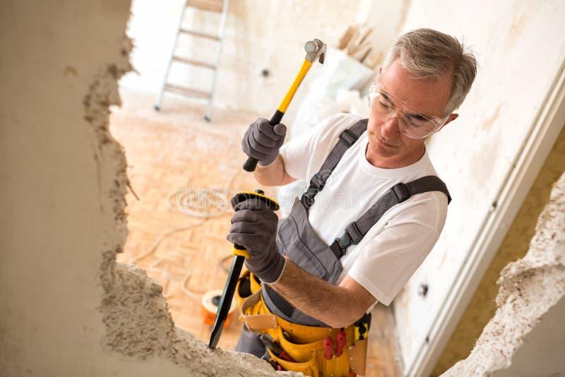 Uomo della costruzione che per mezzo del martello immagine stock libera da diritti