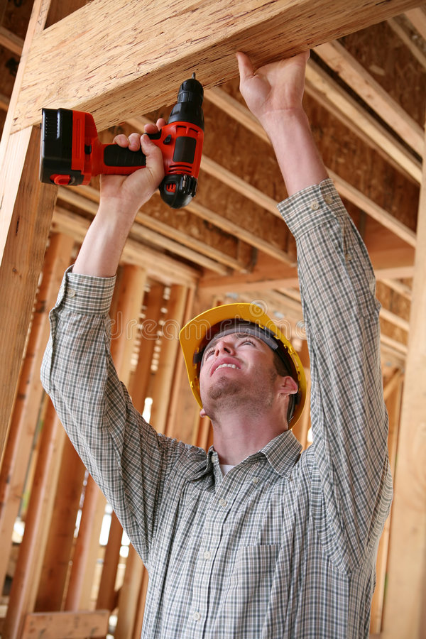 Uomo della costruzione che per mezzo del trivello fotografie stock libere da diritti