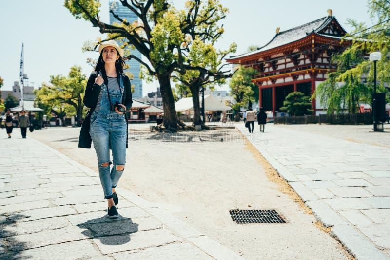 Uomo della lente della ragazza che cammina fuori del tempio fotografie stock libere da diritti