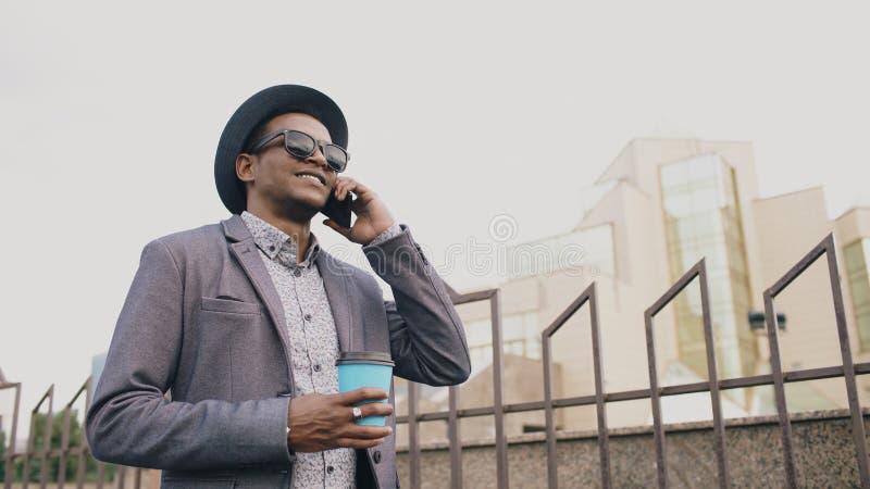 Uomo della mafia in vestito ed occhiali da sole che parlano telefono e che camminano giù la via all'aperto immagine stock libera da diritti