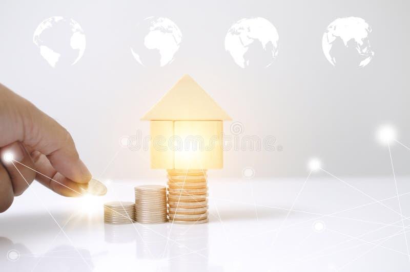 Uomo della mano che pone le monete della pila con il grafico di legno della mappa del cerchio della terra della casa di blocchi e royalty illustrazione gratis