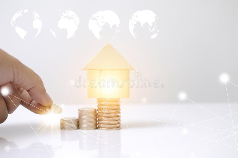 Uomo della mano che pone le monete della pila con il grafico di legno della mappa del cerchio della terra della casa di blocchi e fotografia stock