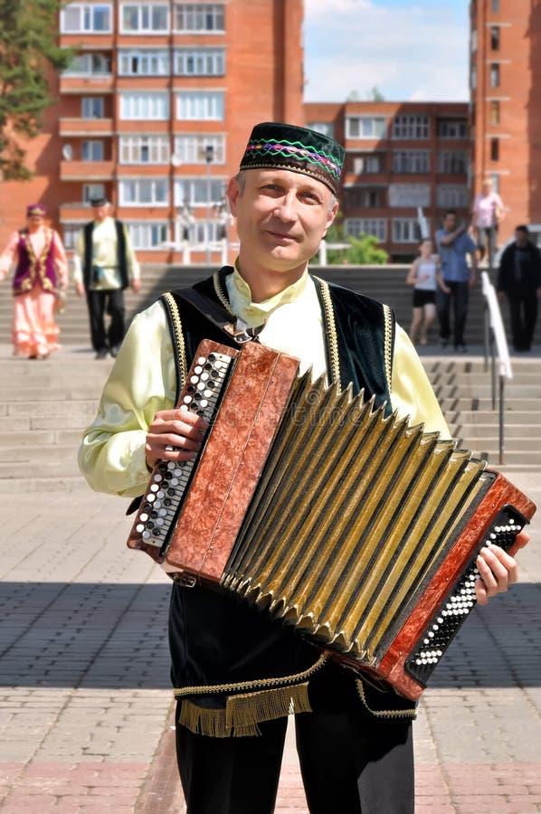 Uomo della nazionalità di Asia centrale in un costume nazionale tartaro con una fisarmonica sulla via della città di Visaginas, fotografie stock